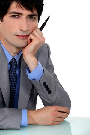 dishy: portrait of young businessman with face resting on hand Stock Photo