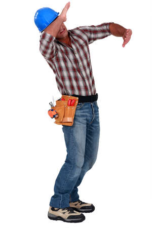 protection hands: Tradesman using his arms to block a blow
