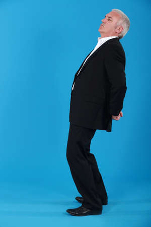 abomination: portrait of mature man standing back in profile against blue background Stock Photo