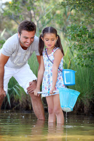 Father and daughter fishing in pond photo