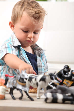 12 18 months: Young boy playing with a selection of toy figurines and animals