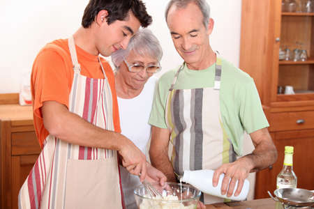 20 years old: a 20 years old boy and 65 years old man and woman making cake together Stock Photo