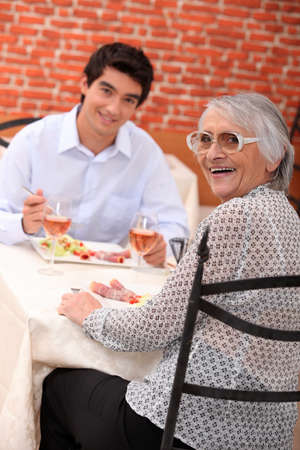 Woman enjoying a meal out with her grandson photo