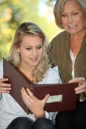 ancestors: Young woman and her grandmother looking at a photo album Stock Photo
