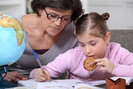 Mother helping her daughter with her homework. photo