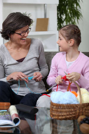 Grandmother knitting with her granddaughter photo