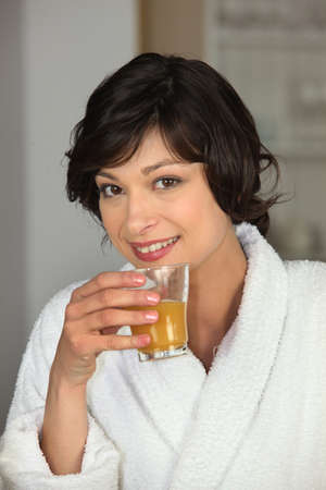 healthfulness: pretty woman in bathrobe having glass of orange juice Stock Photo