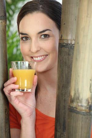 habitos saludables: Sonriente mujer con un vaso de jugo de naranja