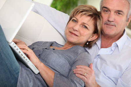 blissful: Middle-aged couple looking at their laptop