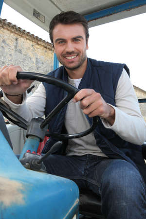 Young farmer driving a tractor photo