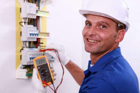 electricista: Electricista comprobar una caja de fusibles Foto de archivo