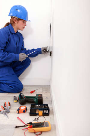voltmeter: Female electrician installing a wall socket