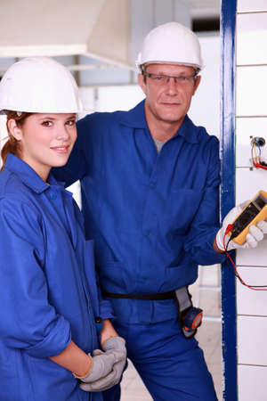 40 45: Young female apprentice electrician Stock Photo
