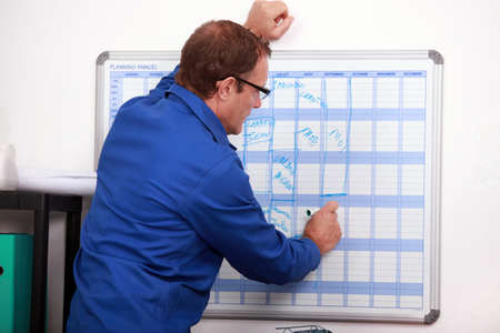 jot: Construction worker writing in deadlines on a calender Stock Photo