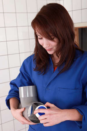 Female plumber with large plastic pipe Stock Photo - 11796567