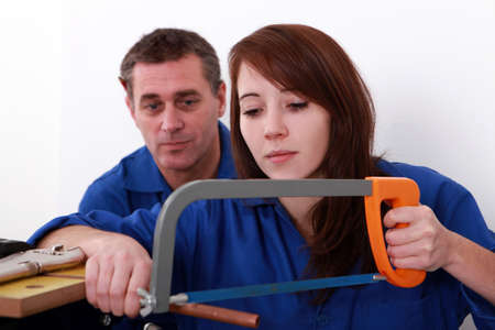 Female apprentice plumber sawing copper pipe Stock Photo - 11797573