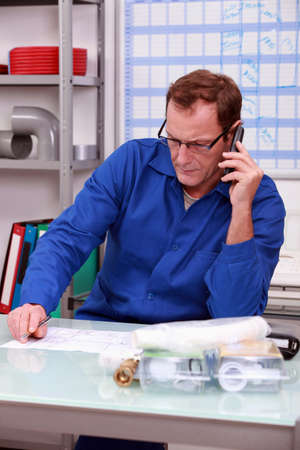 Plumber on the phone in office photo