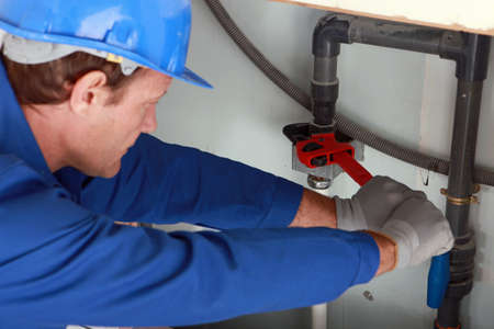 plumbing: Man using a large red wrench on some interior water pipes