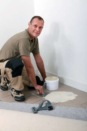 make a paste: Smiling carpet fitter spreading adhesive on an old tiled floor