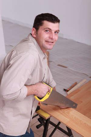 handsaw: Carpenter sawing wooden flooring