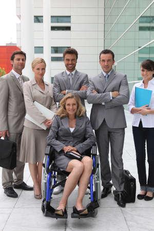 minusv�lidos: mujer en una silla de ruedas y el equipo Foto de archivo