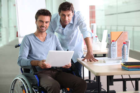 collaborating: Man in wheelchair holding laptop computer next to colleague Stock Photo