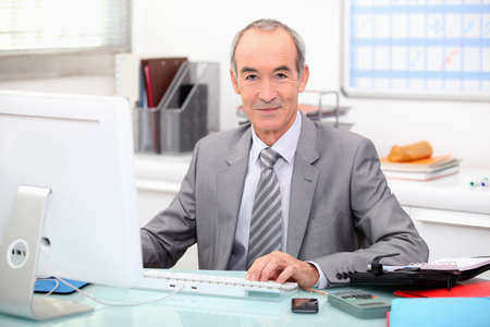Senior businessman working at a computer photo