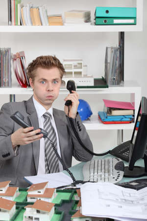 young man overwhelmed with phone calls photo