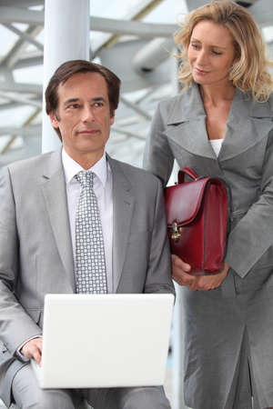 45 49 years: Man using a laptop computer accompanied by a woman with a red briefcase
