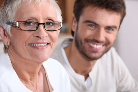 55 to 60: Senior woman in glasses with young man Stock Photo