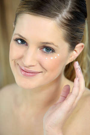 banish: Woman applying eye cream Stock Photo