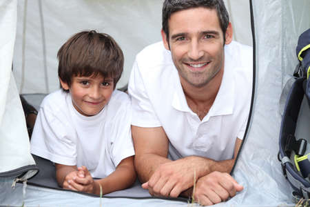 holiday budget: Father and son camping in a tent Stock Photo