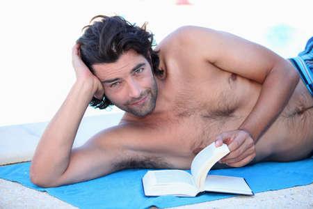 mann mit langen haaren: Ein Mann liest am Strand
