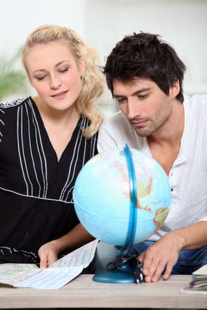 organising: portrait of a couple with map of the world