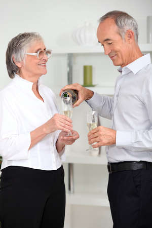 mature man pouring sparkling wine to his wife photo