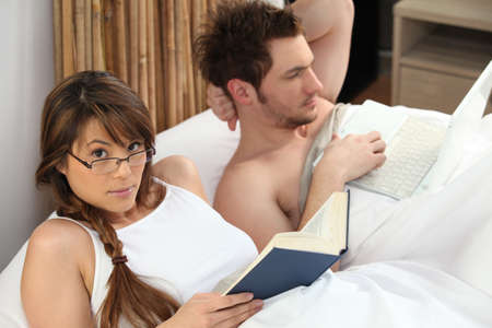 Young woman reading book and man using laptop in bed photo
