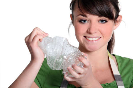 young girl squashing plastic bottle photo