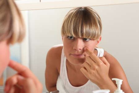 Blond teenage girl in bathroom washing face photo