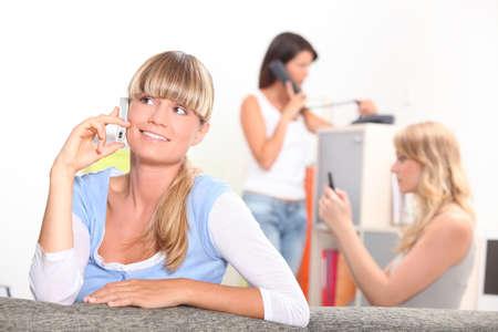Three young women making calls photo