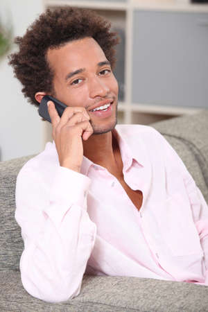 afro american: Young man making a call at home