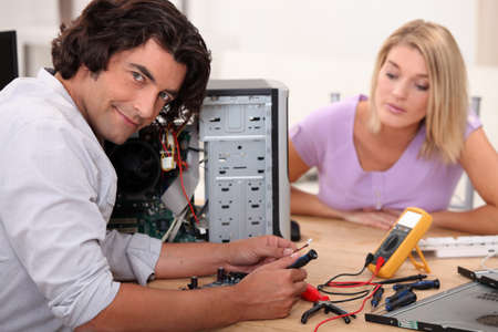 mid long hair man is repairing a computer in front of a blonde woman photo
