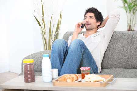 answering call: young man relaxing on the couch and talking on the phone