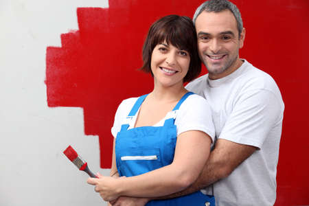conjoin: couple painting a wall in red Stock Photo