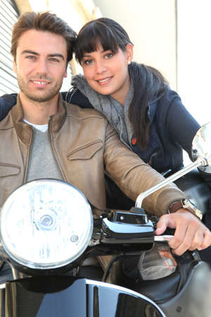 Attractive couple riding scooter photo