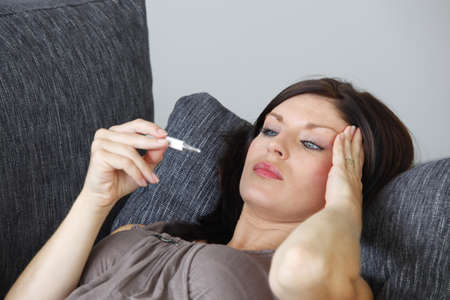 sickly: Woman taking her temperature Stock Photo