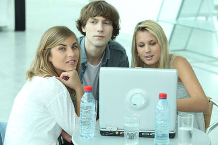 Teenagers sitting round a laptop computer photo