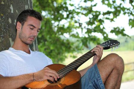sotto l albero: L'uomo suonare la chitarra sotto l'albero Archivio Fotografico