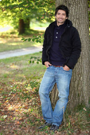 backwoods: young man near a tree in autumn