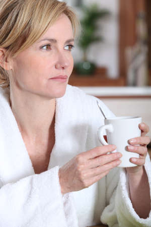 toweling: Pensive woman having a morning cup of coffee in her bathrobe
