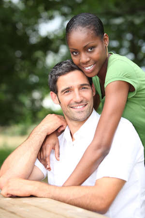 Mixed race couple sitting at a picnic table photo